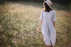 Stylish girl in rustic dress and hat walking among wildflowers in sunny meadow in mountains. Boho woman relaxing in countryside stock image