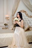 Stylish girl in sexy dress sitting on the bed Royalty Free Stock Image
