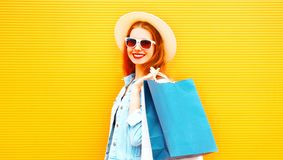 Stylish girl with shopping bags, straw hat on a orange Stock Photo