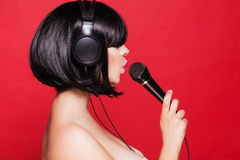 Stylish girl singing with a microphone, red Royalty Free Stock Photo