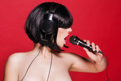 Stylish girl singing with a microphone on red Stock Images