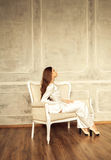 Stylish girl is sitting in a chair Royalty Free Stock Photo