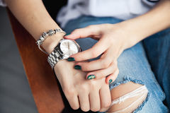 Stylish girl sitting in torn jeans and green modern manicure, bridge silver watch, bracelet. Fashion, lifestyle, beauty, apparel. And Royalty Free Stock Image