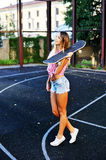Stylish girl with skateboard outdoor Stock Images