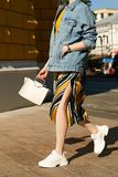 Stylish girl in a skirt, denim jacket and white sneakers in a hurry, swinging her bag. Street lifestyle. royalty free stock image