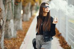 Stylish girl smoking an e-cigarette. As she is walking through the city royalty free stock photos