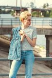 stylish girl standing on bridge in jeans and denim vest stock image