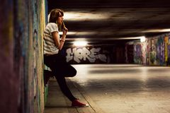 Stylish girl standing in grunge graffiti tunnel, shanty town Stock Images