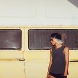 Stylish girl stands near minibus. Surf fashion style royalty free stock photo