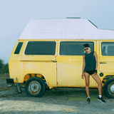 Stylish girl stands near vintage minibus. Urban fashion style Stock Photos