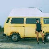 Stylish girl stands near vintage minibus. Urban fashion style stock photos