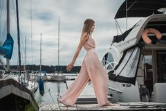 Stylish girl steps wide step along the pier on the background of yachts royalty free stock images