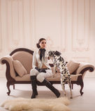Stylish girl in a suit rider. Poses with Dalmatian. Creative colors Royalty Free Stock Photography