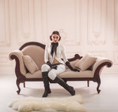 Stylish girl in a suit rider. Strict, beautiful girl in elegant rider suit poses on camera. Restrained interior, vintage sofa. Unusual hairstyle and makeup Royalty Free Stock Image