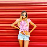 Stylish girl in sunglasses posing over red wall Royalty Free Stock Images