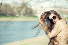 Stylish girl sunny day outdoor. Stylish girl wearing sunglasses and scarf outdoor in sunny spring or autumn day near water, copy scape Stock Images