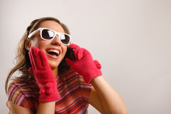 Stylish girl talking on the phone. Modern looking young woman wearing sun glasses Stock Image