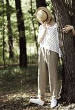 Stylish girl teenager covers her face with a straw hat. Near a tree in the forest Stock Photo