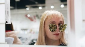 Stylish girl tries on beautiful glasses in front of the mirror. Nice close-up. Good mood. stock video footage