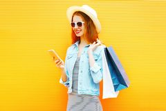 Stylish girl is using the smartphone in the city on orange Stock Image