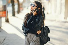 Stylish girl walking through the city while using her phone stock images
