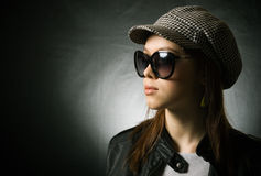 Stylish girl wearing cap. A pretty girl in a cap and sunglasses on a dark background Stock Images