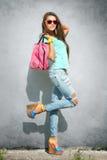 Stylish girl. Stylish young girl posing against gray wall Royalty Free Stock Photo