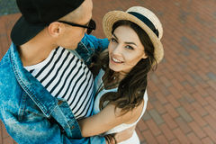 Stylish girlfriend in straw boater and her boyfriend hugging on the street Stock Images