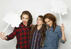 Stylish girls best friends holding blank paper on stick. Stock Images