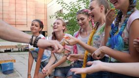 Stylish girls with bright braids playing of spinners outdoors, company of friends showing trick with fidget spinners stock video