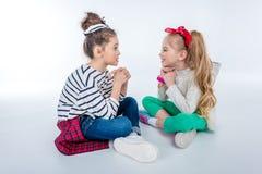 Stylish girls talking while sitting on floor on grey Royalty Free Stock Photos