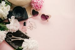 Stylish girly flat lay with pink peonies, photo camera, retro sunglasses, jewelry, nail polish, hat, purse on pastel pink paper. With copy space. International royalty free stock images