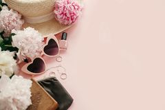 Stylish girly image of pink retro sunglasses,peonies, jewelry, nail polish, hat, purse on pastel pink paper with copy space. Hello spring concept. Summer royalty free stock photography