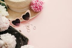 Stylish girly pink retro sunglasses,peonies, jewelry, hat, purse on pastel pink paper with copy space. Hello spring concept. Summer vacation. International stock images
