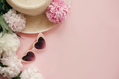 Stylish girly pink retro sunglasses, white and pink peonies, straw hat on pastel pink paper with copy space. Hello spring concept. Summer vacation flat lay stock image