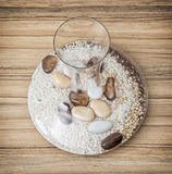 Stylish glass vase full of decorative stones on the wooden backg Royalty Free Stock Photography