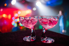Stylish glasses with ice at party with colorful blurred background Stock Photos