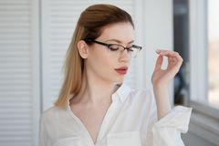 Stylish glasses in a thin frame, vision correction. Portrait of a young woman. In business style stock photography