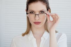 Stylish glasses in a thin frame, vision correction. Portrait of a young woman. In business style stock photos