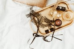 Stylish gold tray and black mask on soft bed. flat lay woman essentials for a holiday. Instagram photo Royalty Free Stock Photos