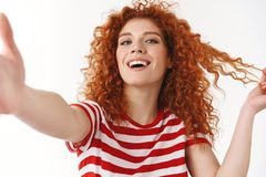 Stylish good-looking cheeky redhead curly blue-eyed woman smiling white teeth playing hairstyle flirty laughing record. Emotions video hold camera hand towards royalty free stock photography