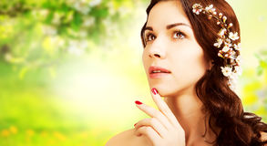 Stylish gorgeous brown haired woman with blooming branch with gr Royalty Free Stock Images
