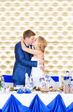 Stylish gorgeous happy bride and groom kissing at wedding reception, emotional cheerful moment Stock Images