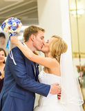 Stylish gorgeous happy bride and groom kissing at wedding reception, emotional cheerful moment Royalty Free Stock Image