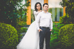 Stylish gorgeous happy brunette bride and elegant groom on the b Royalty Free Stock Images