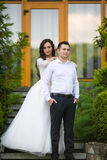 Stylish gorgeous happy brunette bride and elegant groom on the b Royalty Free Stock Photography