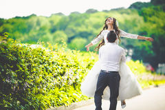 Stylish gorgeous happy brunette bride and elegant groom walking Royalty Free Stock Images