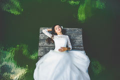 Stylish gorgeous happy brunette bride on the pier on the background of a lake royalty free stock images
