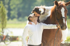 Stylish gorgeous happy brunette bride riding a horse and kissing. Stylish gorgeous happy brunette bride riding a horse and elegant groom on the background of a Stock Image