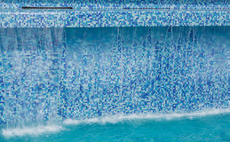 stylish gorgeous modern ceramic, mosaic tiles swimming pool high wall with flowing water Royalty Free Stock Images